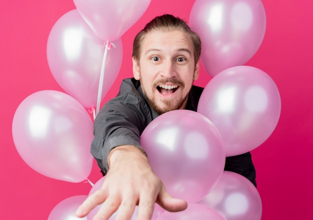 Young man celebrating birthday party holding balloons amazed and surprised  over pink