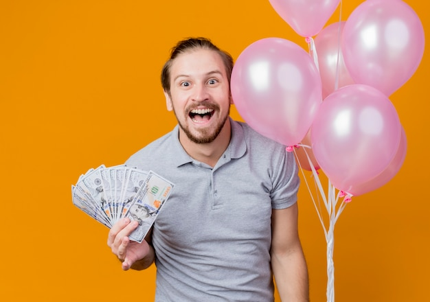 Young man celebrating birthday party holding bunch of balloons showing cash happy and excited standing over orange wall
