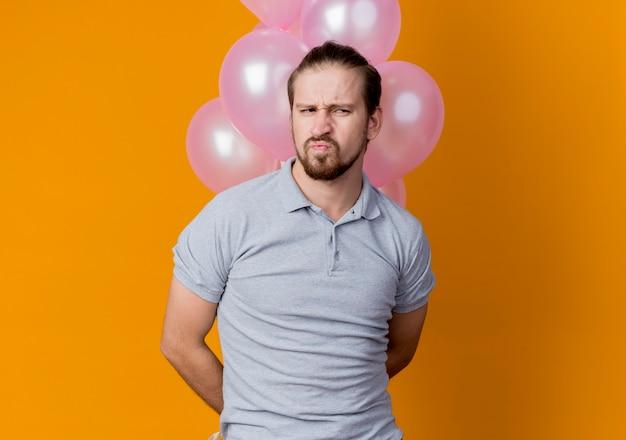 オレンジ色の壁の上に立って不機嫌と不幸を脇に見て風船の束を保持している誕生日パーティーを祝う若い男