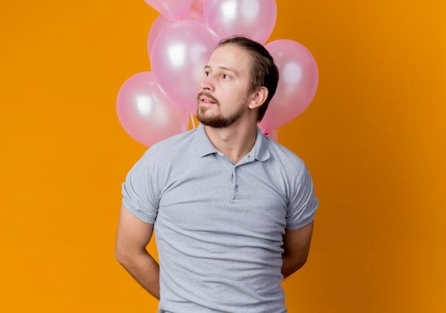 오렌지 벽 위에 서있는 잠겨있는 식으로 옆으로 찾고 풍선의 무리를 들고 생일 파티를 축하하는 젊은 남자