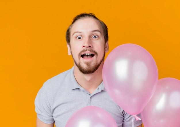 オレンジ色の壁の上に立って驚いた風船の束を保持している誕生日パーティーを祝う若い男