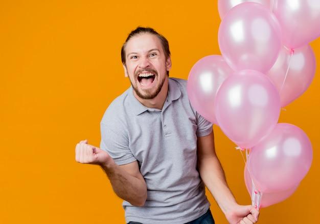 Молодой человек празднует день рождения, держа кучу воздушных шаров, сжимая кулак, сумасшедший, счастливый и взволнованный, кричащий, стоя над оранжевой стеной