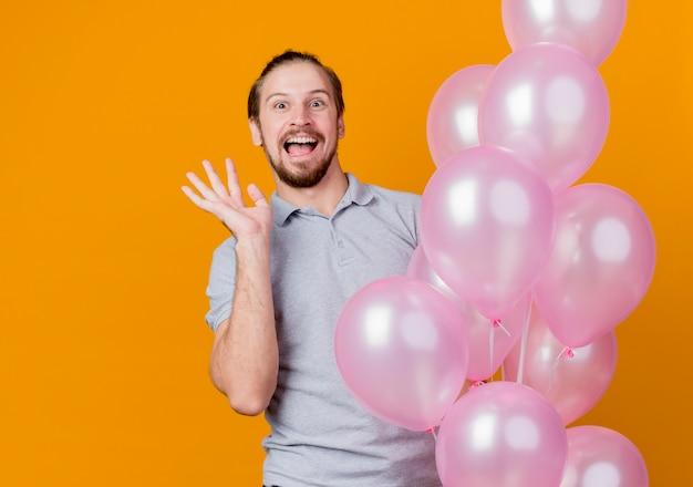 Balloonshapy의 무리를 들고 생일 파티를 축하하는 젊은 남자와 오렌지 벽 위에 유쾌하게 서있는 흥분된 미소