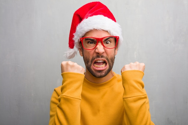 Young man celebrating christmas day holding gifts screaming very angry and aggressive
