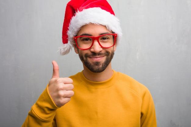 웃 고 엄지 손가락을 올리는 선물을 들고 크리스마스를 축 하하는 젊은이