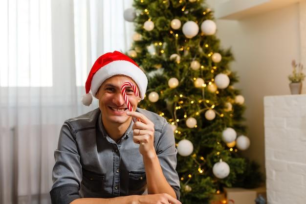 Молодой человек празднует рождество на кухне