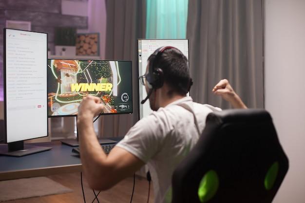 彼の勝利を祝う若い男は彼の拳をきつく保つオンラインシューティングゲーム。