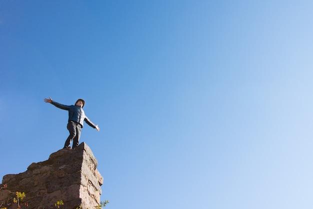コピースペースがたくさんある澄んだ青い空に腕を広げて、高い古い石の壁の上に立っている廃墟の建物で祝う若い男、下からの眺め