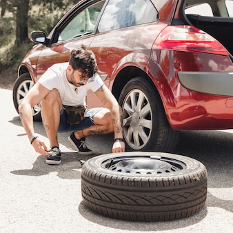 Young man changing the tire of broken down red car