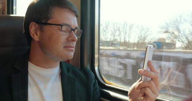 若い男が電車の中でセル上でチャット