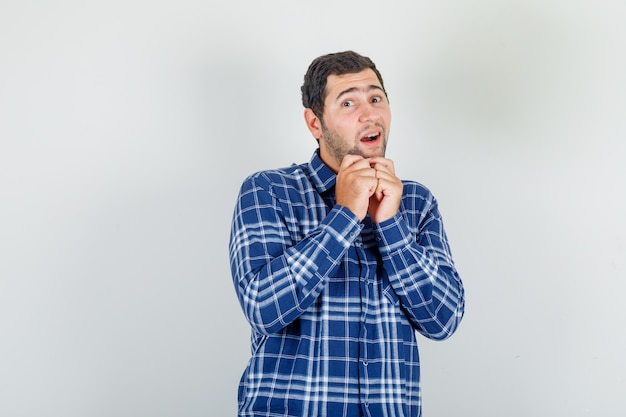 Young man in checked shirt asking for something in cute pose