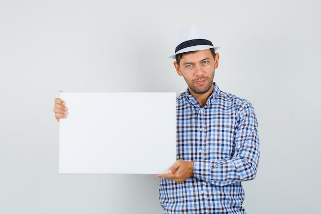 Giovane uomo in camicia a quadri, cappello tenendo tela vuota e guardando fiducioso