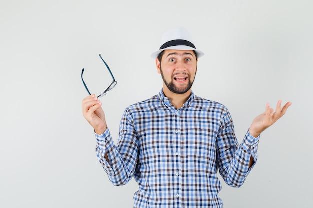 Giovane uomo in camicia a quadri, cappello con occhiali e guardando eccitato