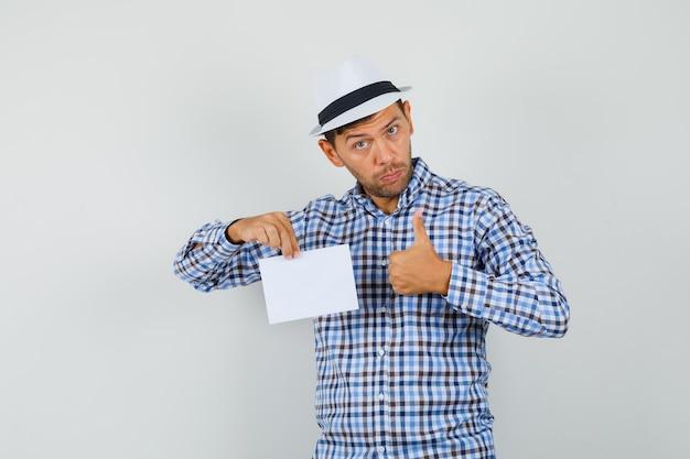 Giovane uomo in camicia a quadri, cappello tenendo il foglio di carta