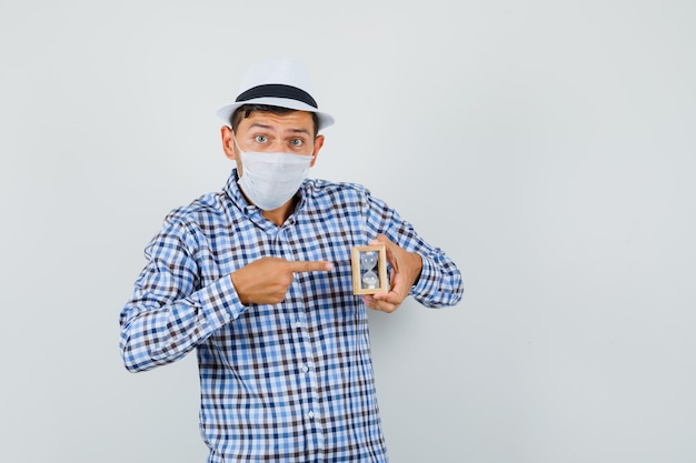 Young man in checked shirt, hat, mask pointing at hourglass and looking worried