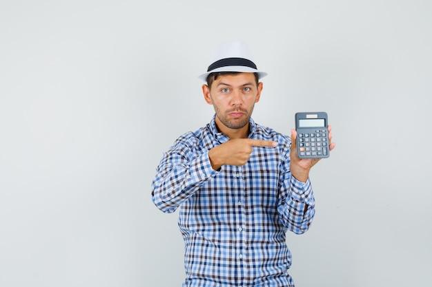 Giovane uomo in camicia a quadri, cappello che punta alla calcolatrice e che sembra serio