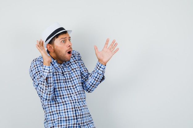 Giovane uomo in camicia a quadri, cappello alzando le mani in gesto perplesso