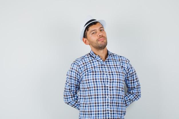 Giovane uomo in camicia a quadri, cappello in piedi con le mani sulla schiena e guardando fiducioso