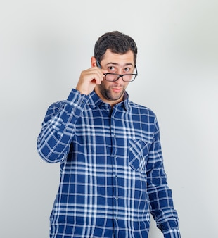 Young man in checked shirt looking at camera over glasses and looking surprised