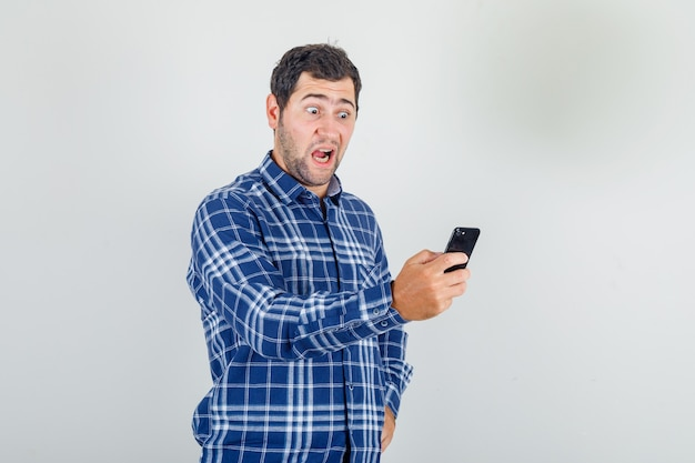 Young man in checked shirt looking at smartphone in his hand and looking shocked