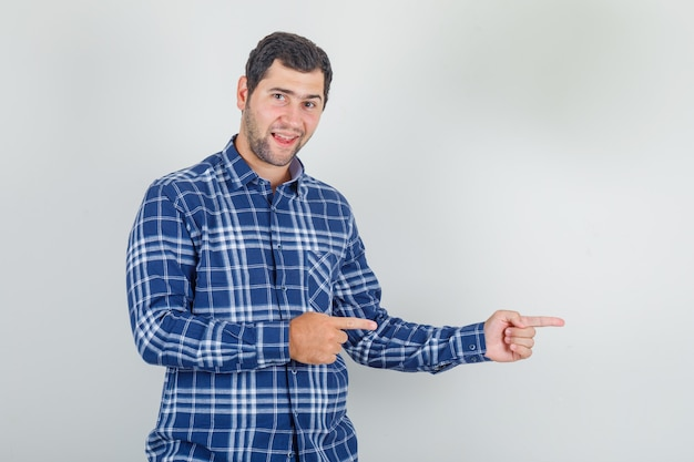 Young man in checked shirt pointing fingers away and looking happy