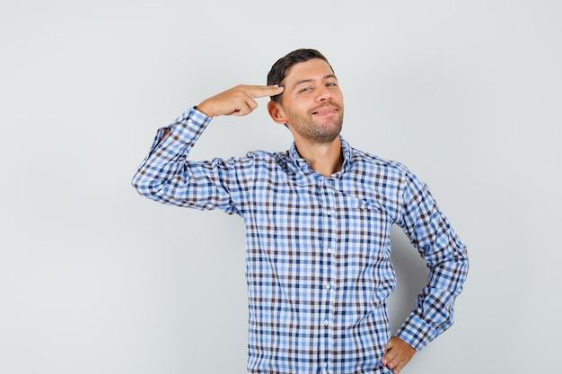 Giovane uomo in camicia a quadri che punta la mano e le dita alla testa e sembra allegro