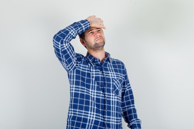 Young man in checked shirt suffering from headache with hand on forehead