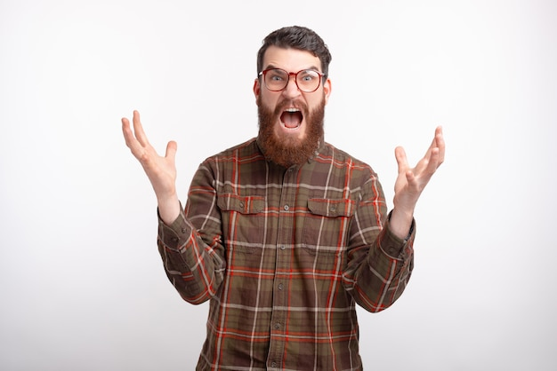 Young man in checkered shirt gesturing angry over white background and looking at the camera