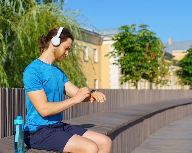 Молодой человек проверяет пульс на умных часах во время отдыха после тренировки на открытом воздухе