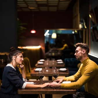 Young man and cheerful woman holding hands at table with glasses of wine in restaurant