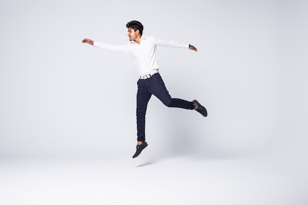 Young man cheering and jumping over white wall