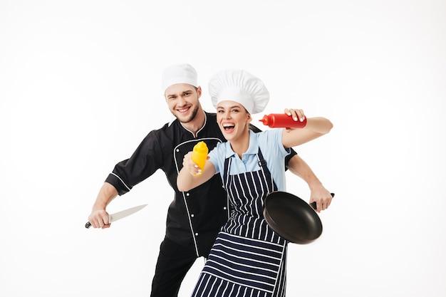 손에 칼과 팬을 들고 검은 제복을 입은 젊은 남자 요리사와 예쁜 여자가 케첩과 겨자 병을 장난스럽게 들고 줄무늬 앞치마에 요리합니다.