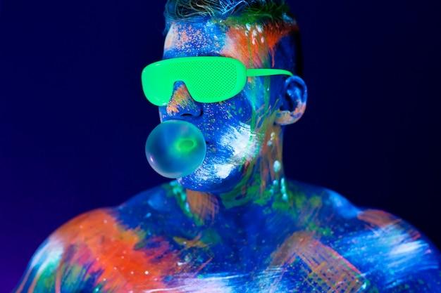 Молодой человек жует жвачку и раздувает воздушный шар. флуоресцентная краска на лице в студии с ультрафиолетом