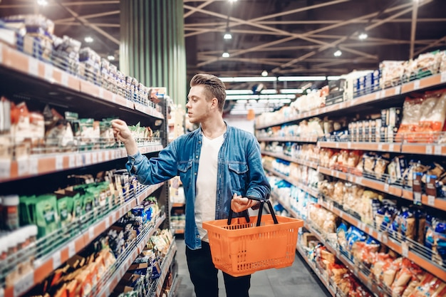 Young man chooses foods at the supermarket