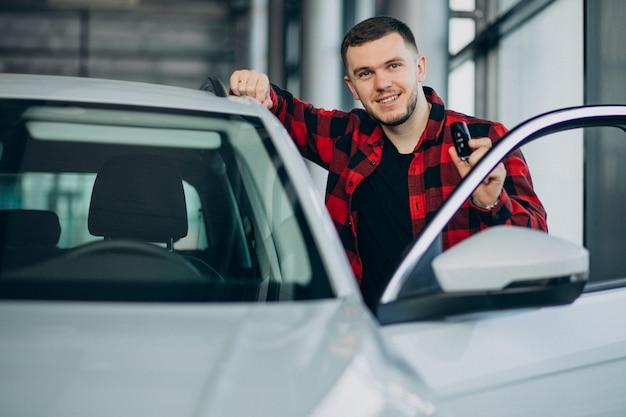 Молодой человек выбирая автомобиль в автосалоне