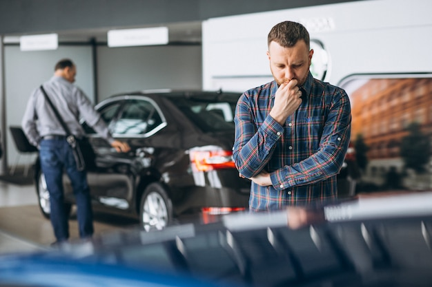 Young man choosing a car in a car showroom