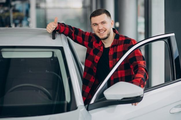 Giovane che sceglie un'automobile in una sala d'esposizione dell'automobile