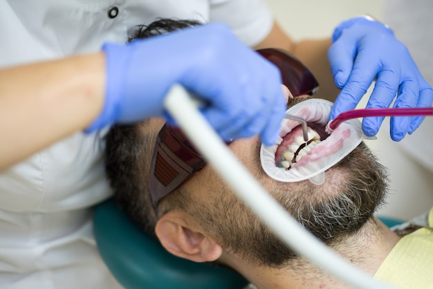 Молодой человек, выбирая цвет зубов у стоматолога. стоматолог, исследующий зубы пациента в клинике