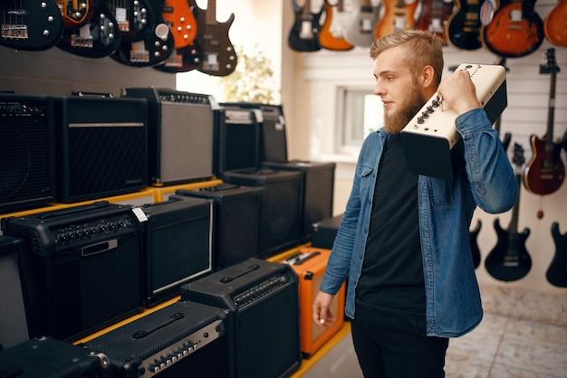 Young man choosing combo amplifier for electric guitar in music store.