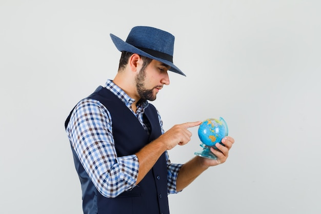 Young man choosing destination on globe in shirt, vest, hat and looking pensive. .