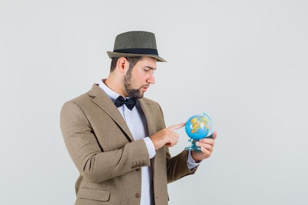 Giovane che sceglie la destinazione sul globo in vestito, cappello e che sembra pensieroso. vista frontale.