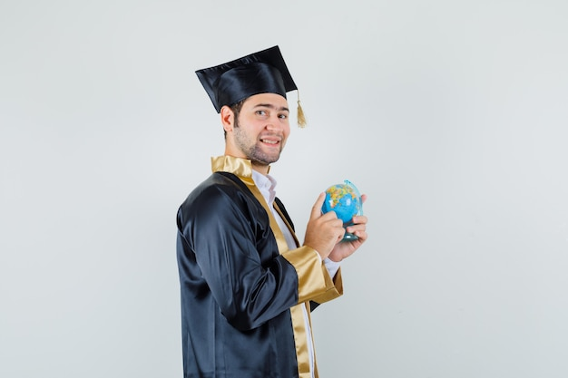 Young man choosing destination on school globe in graduate uniform and looking jolly. .