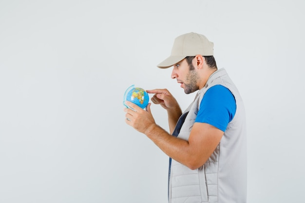 Young man choosing destination on school globe in t-shirt, jacket and looking amazed .