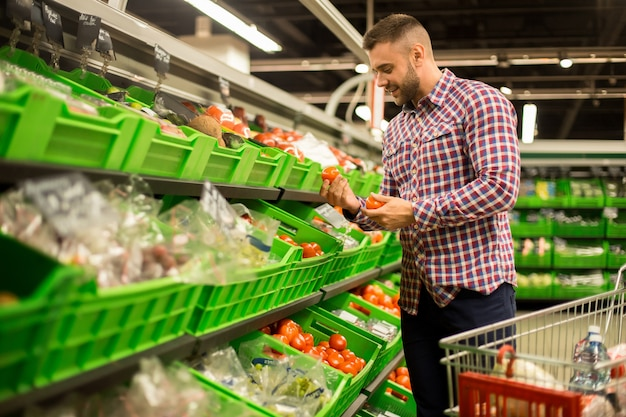 若い男がスーパーで新鮮なトマトを選ぶ