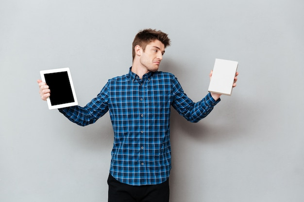 Young man choosing between tablet computer and book.