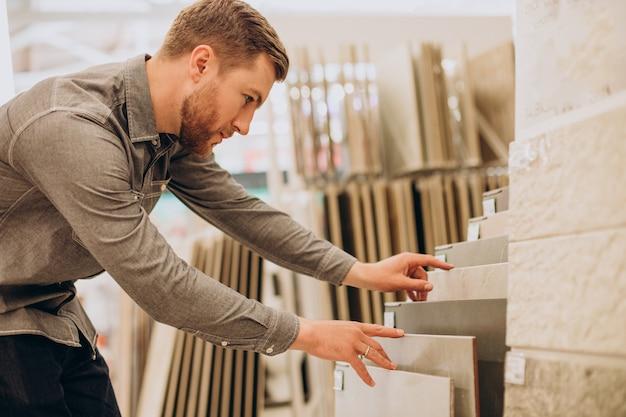 Молодой человек выбирает плитку на строительном рынке