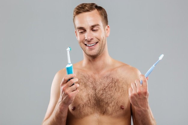 Young man choosing toothbrush isolated on the gray wall