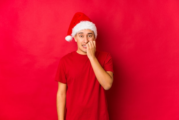 Young man on christmas day biting fingernails, nervous and very anxious.