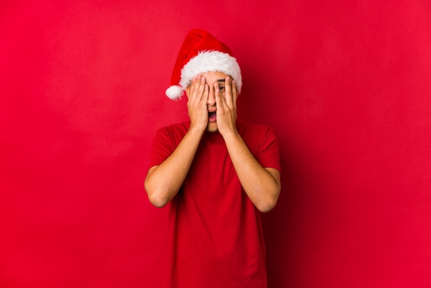 Young man on christmas day blink through fingers frightened and nervous.