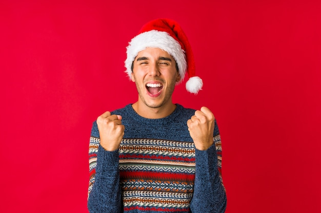 Young man on christmas day covering ears with hands.